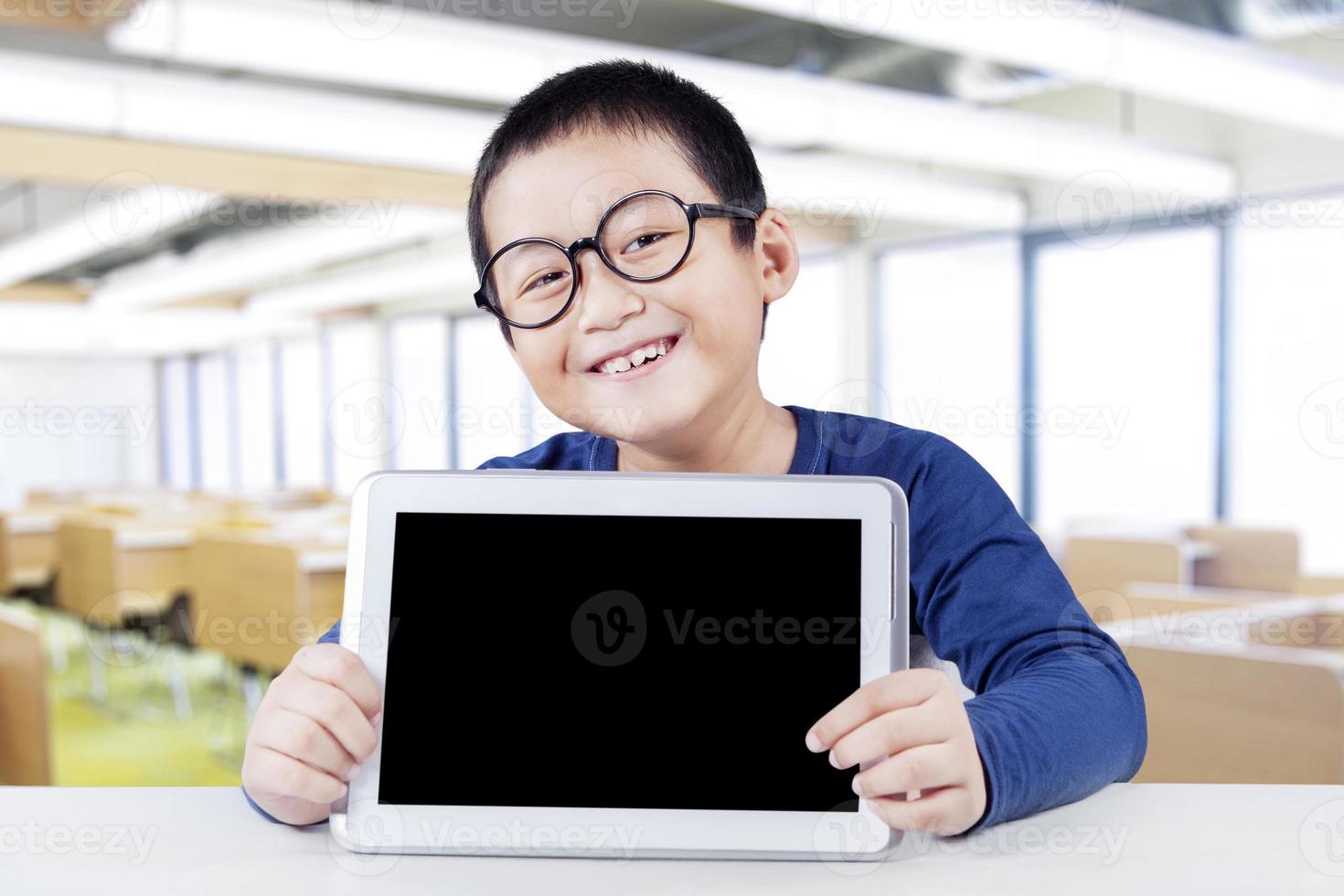 glücklicher Schüler mit leerem Tablettbildschirm foto