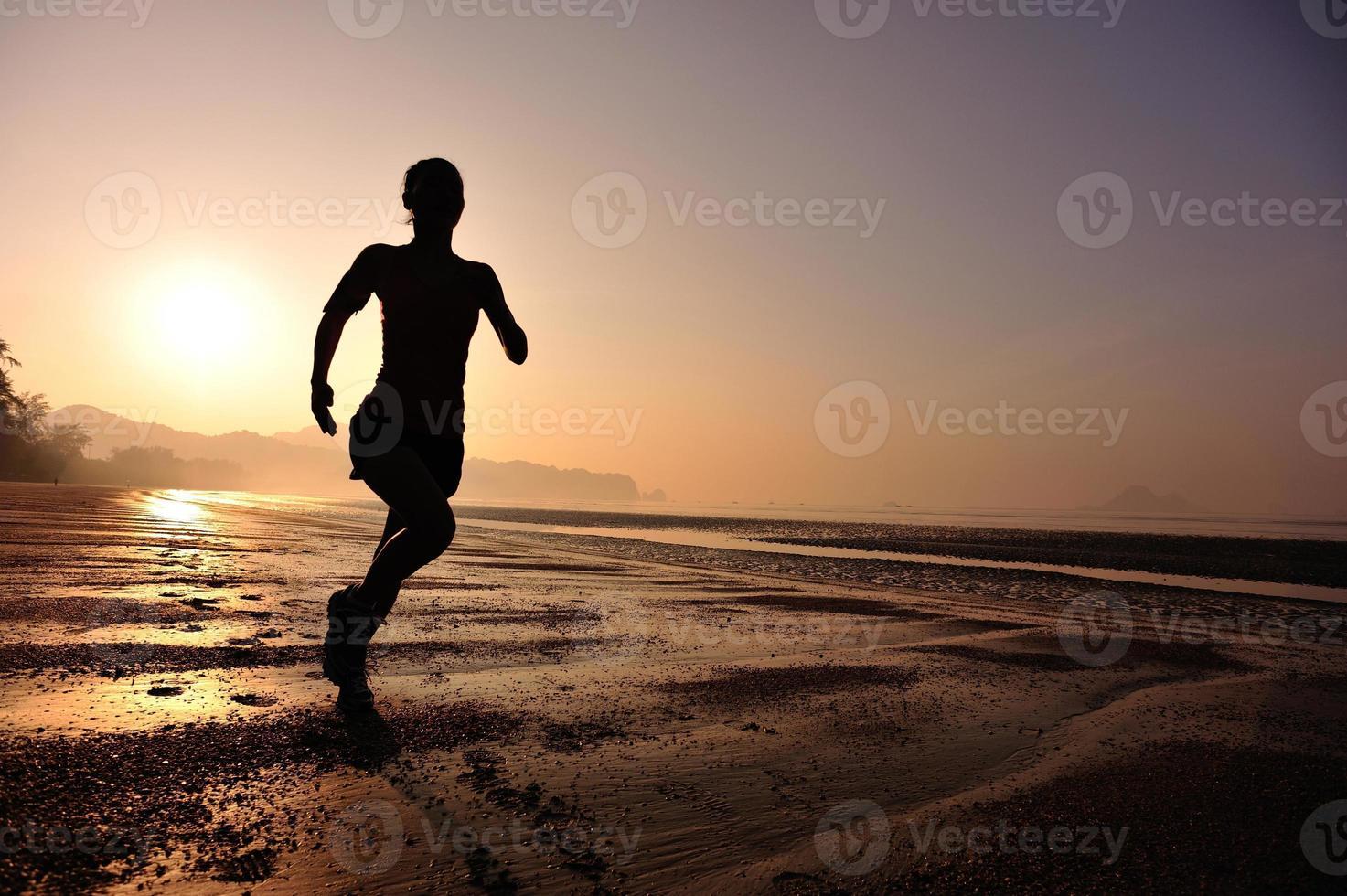 junge Fitnessfrau, die am Sonnenaufgangstrand läuft foto
