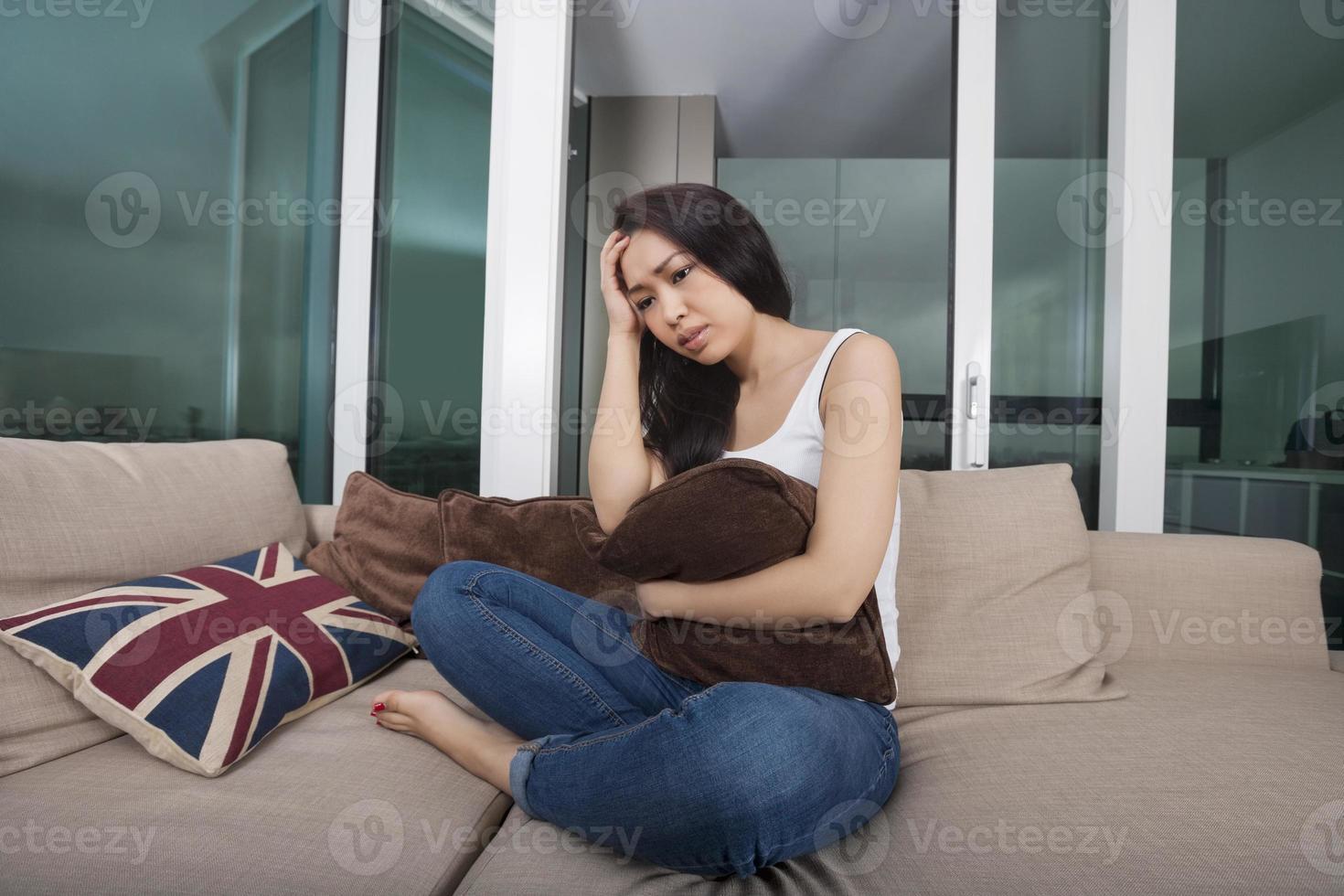 volle Länge der besorgten jungen Frau, die auf Sofa sitzt foto