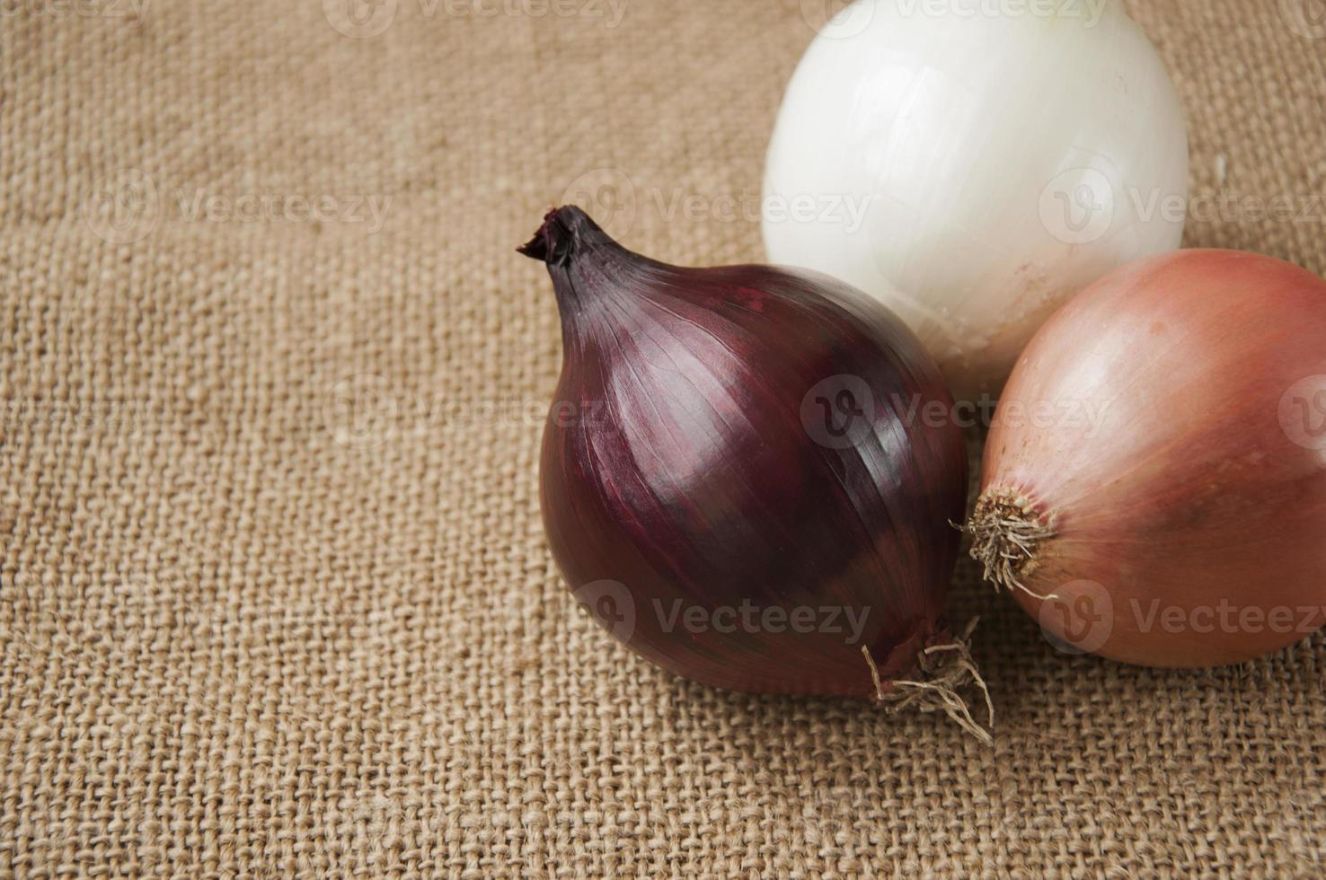 verschiedene Zwiebeln auf einem Hintergrund entlassen, Sackleinen foto