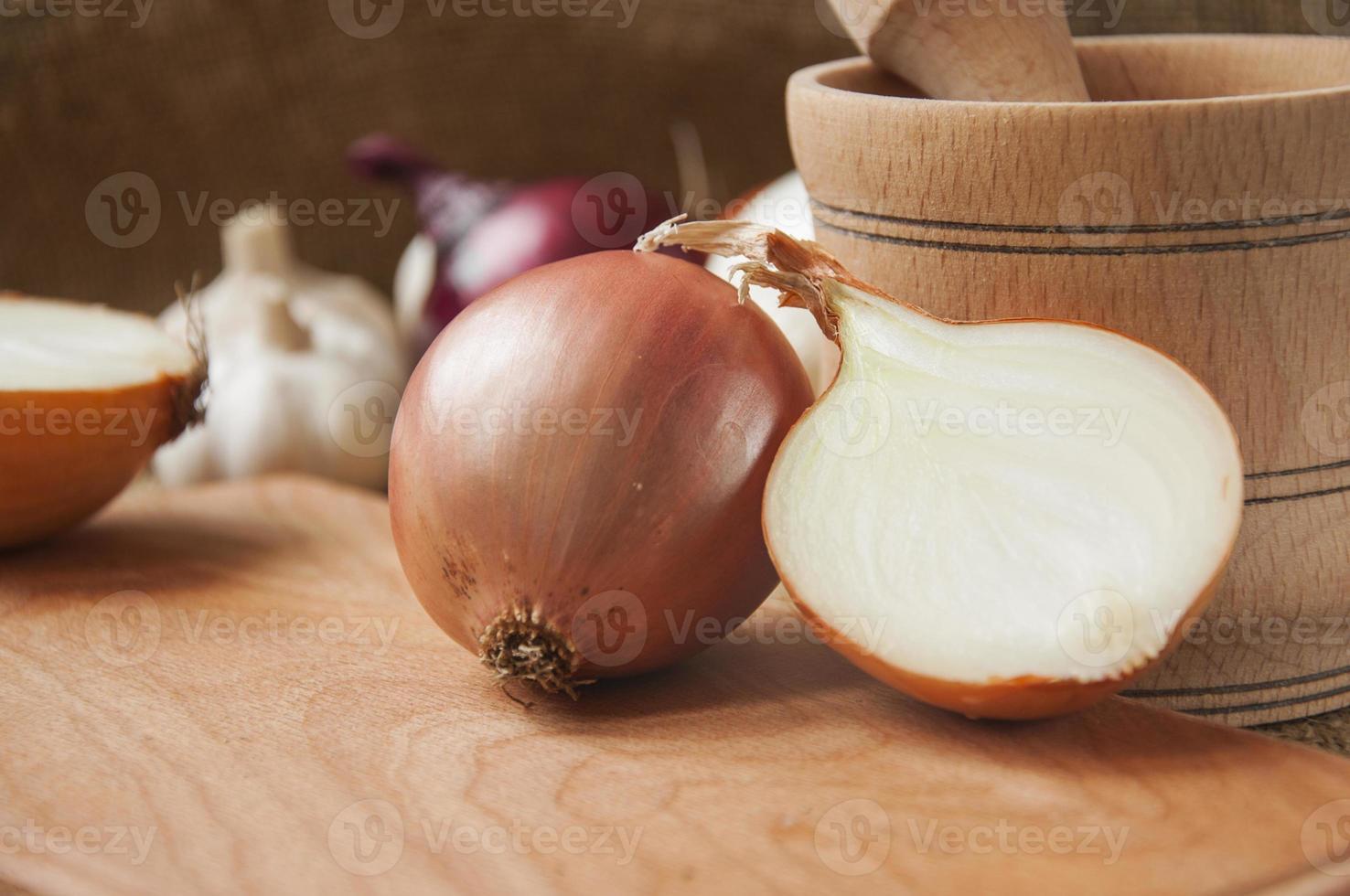 verschiedene Zwiebeln auf einem Brett auf einem Hintergrund entlassen, Sackleinen foto