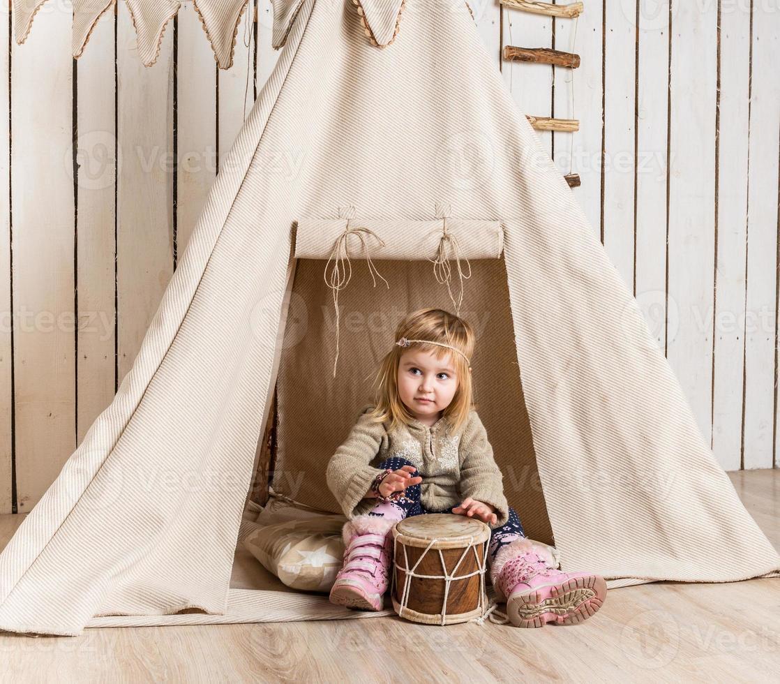 kleines Mädchen mit Trommel in der Nähe von Wigwam foto