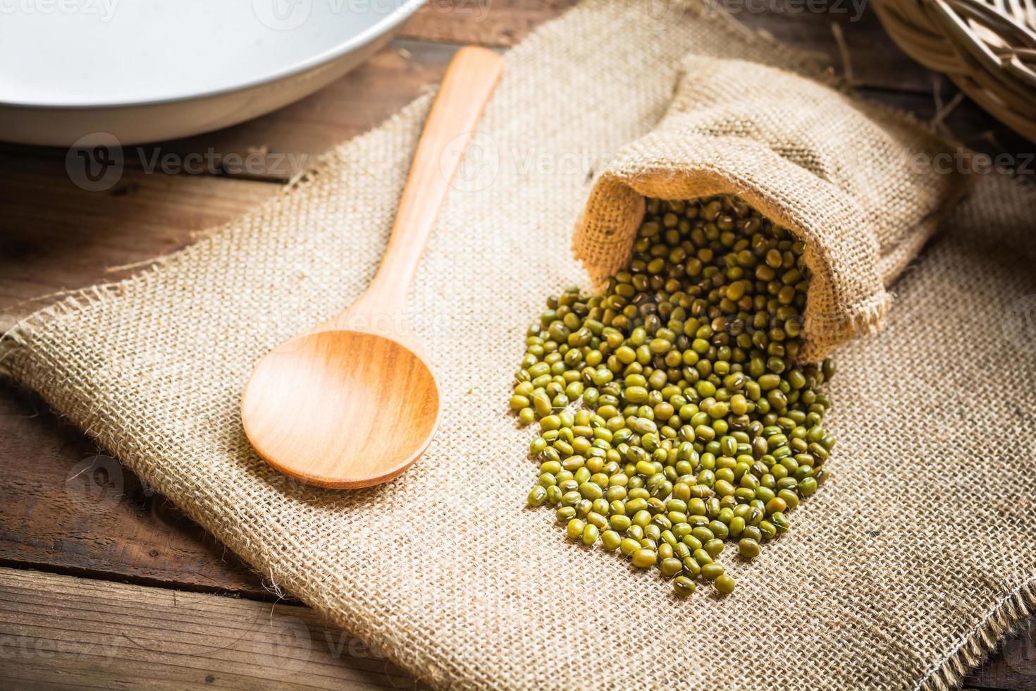 grüne Bohnen in Sackbeuteln und Löffel foto