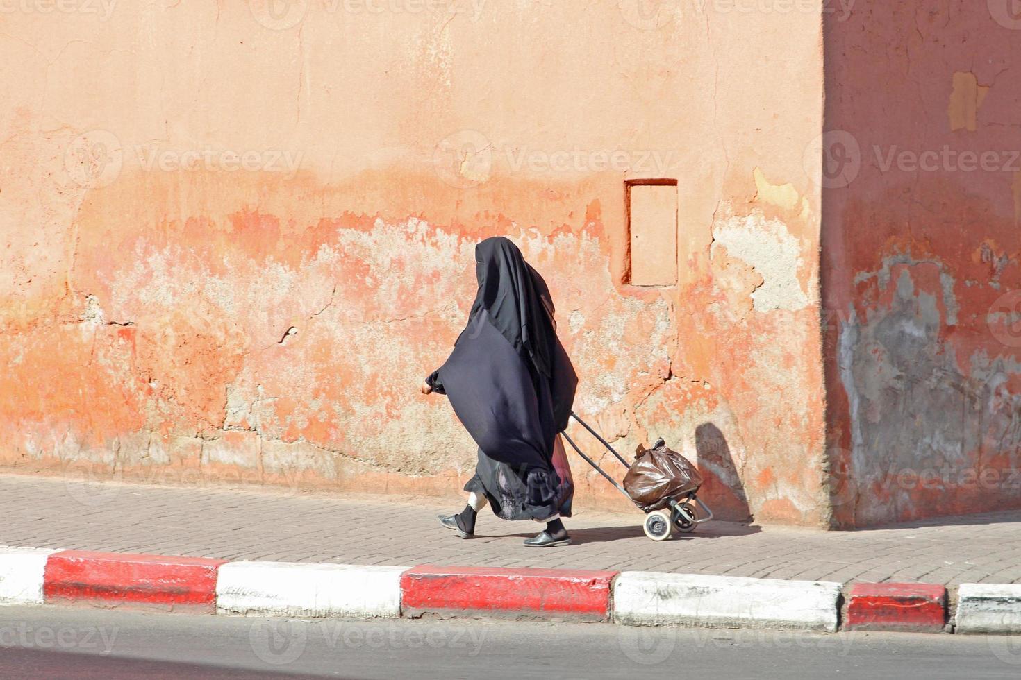 muslimische Frau, die die Straße entlang geht foto