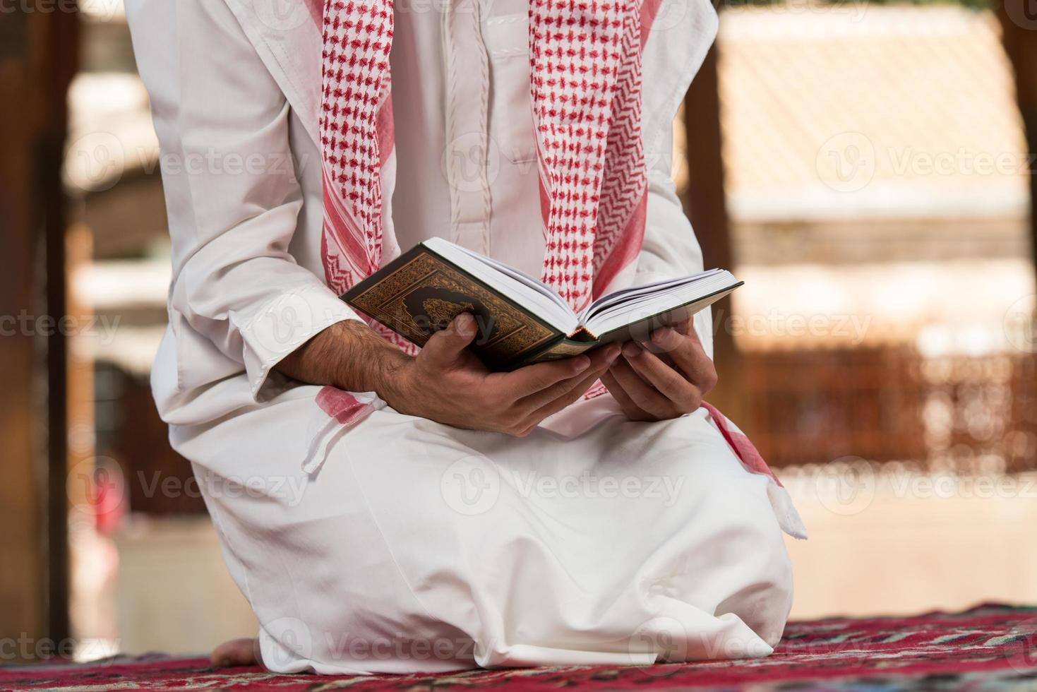 Der muslimische Mann in Dishdasha liest den Koran foto