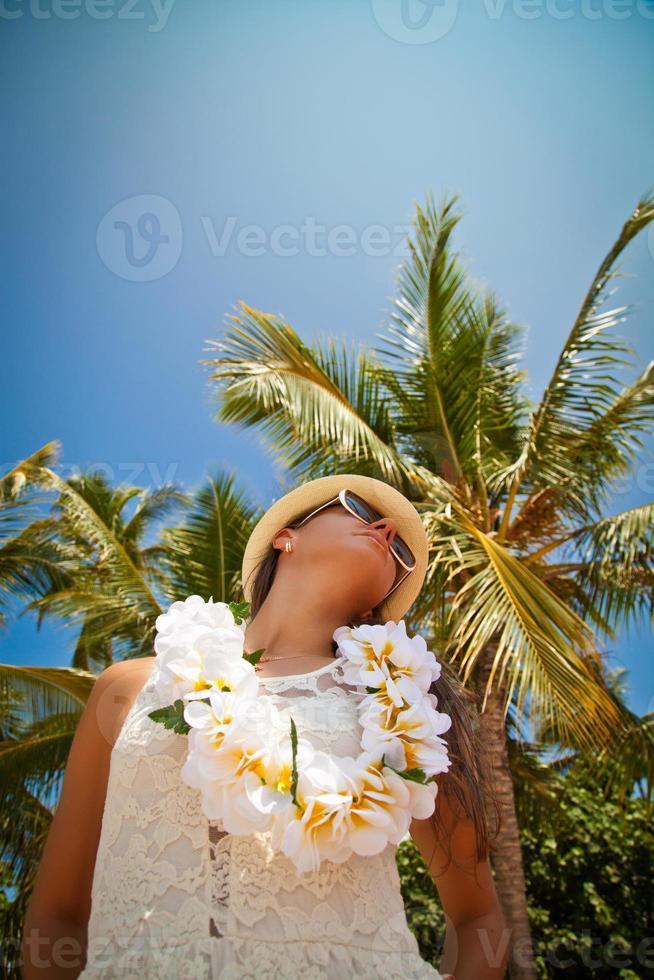 schönes Mädchen, das am Strand in der heißen Sonne aufwirft foto