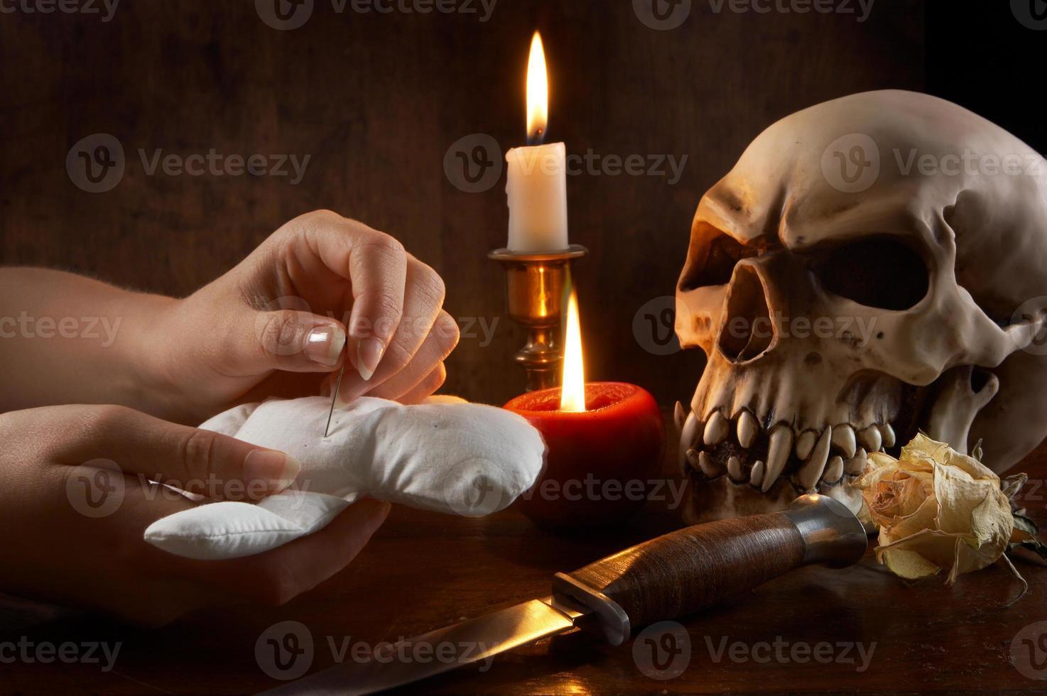 Hände stecken eine Nadel mit Schädel und Messer in eine Voodoo-Puppe foto