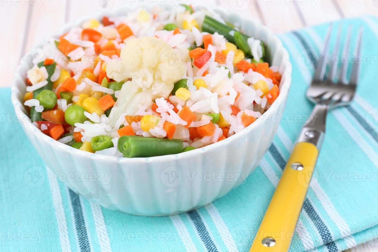 gekochter Reis mit Gemüse auf Holztisch nah oben foto