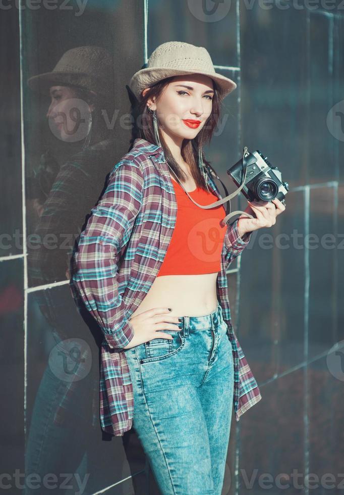 junges schönes Hipster-Mädchen mit Retro-Kamera foto
