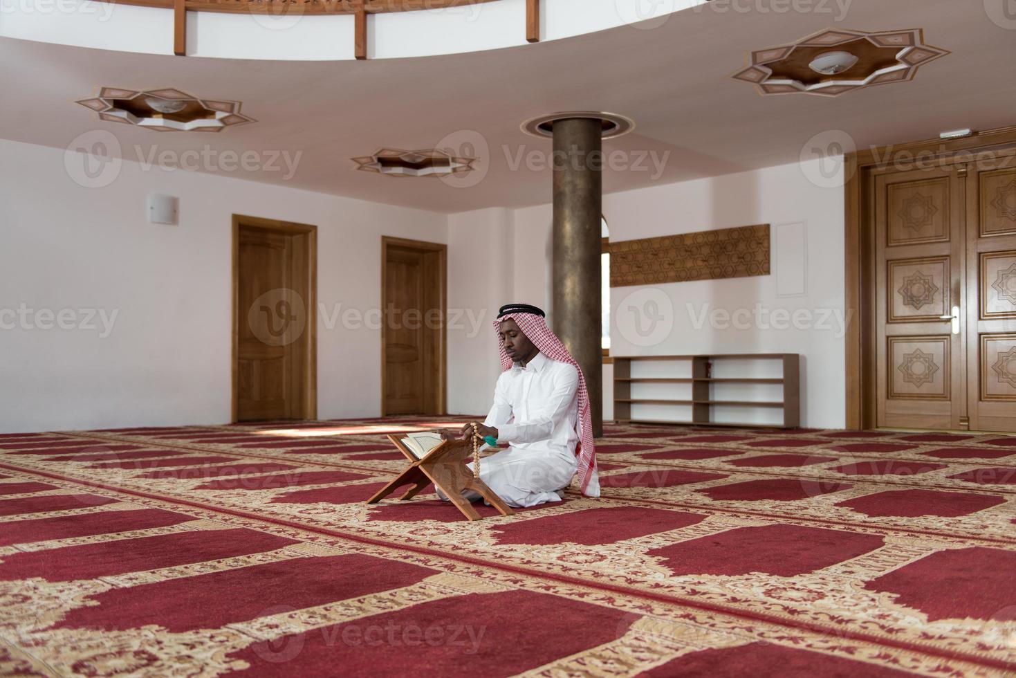 schwarzer Geschäftsmann in Dishdasha liest den Koran foto