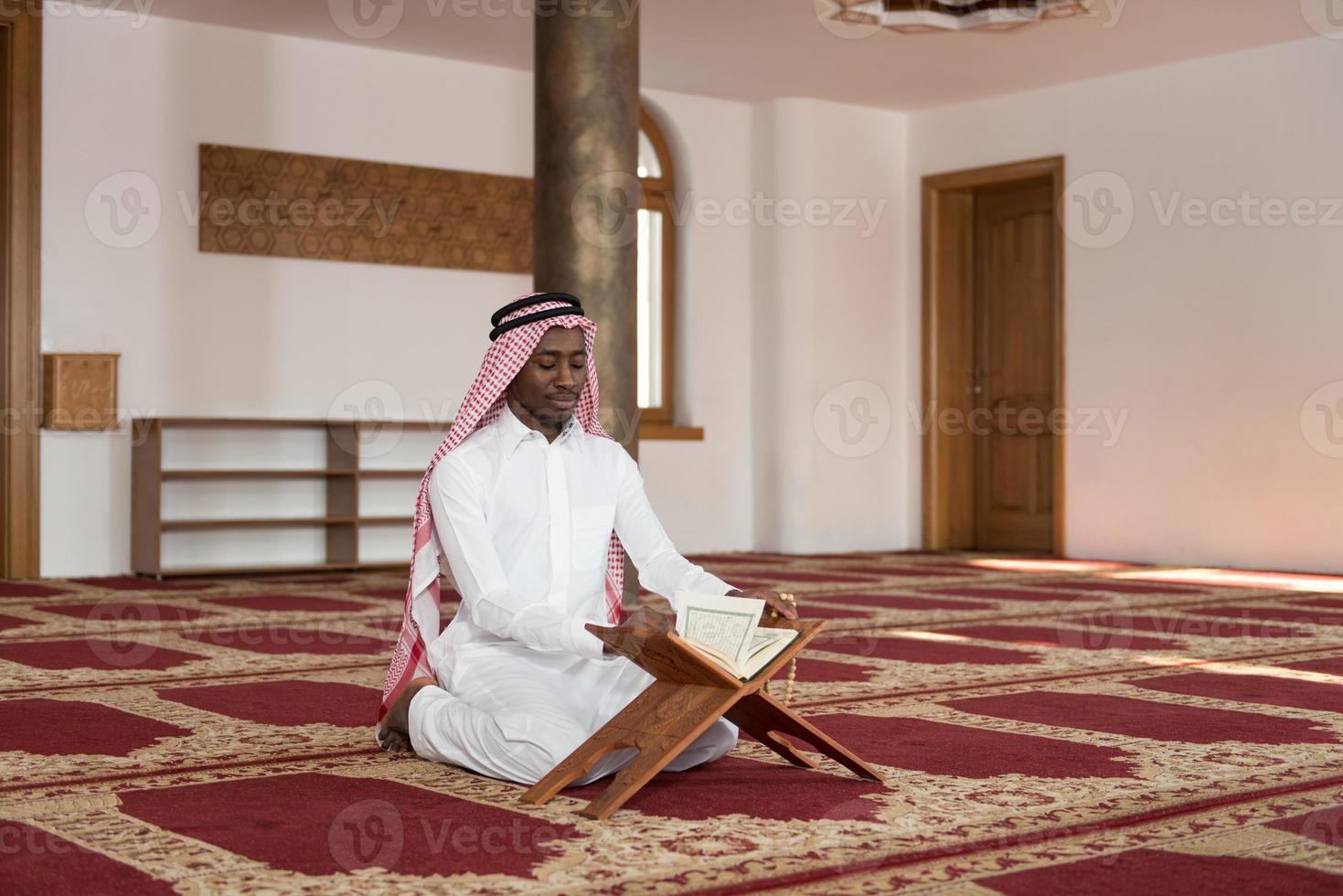 schwarzer Geschäftsmann, der den Koran liest foto