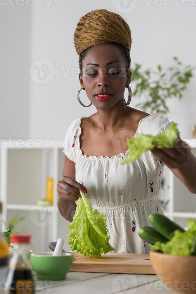 Frau, die Gemüse für Salat hackt foto