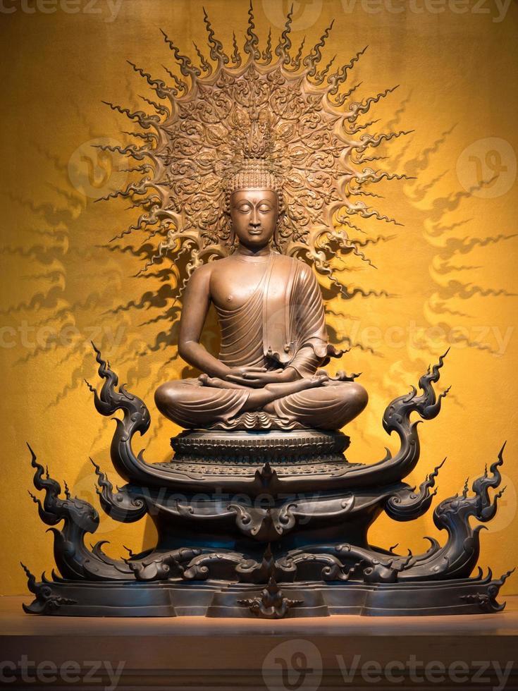 goldene Buddha-Skulptur im Lotussitz sitzend foto