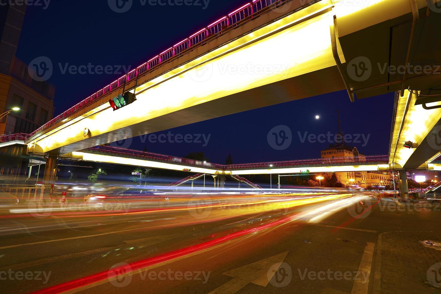 städtische Fußgängerbrücke und Straßenkreuzung der Nachtszene foto
