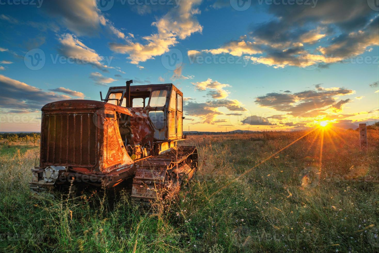 alter rostiger Traktor in einem Feld auf Sonnenuntergang foto