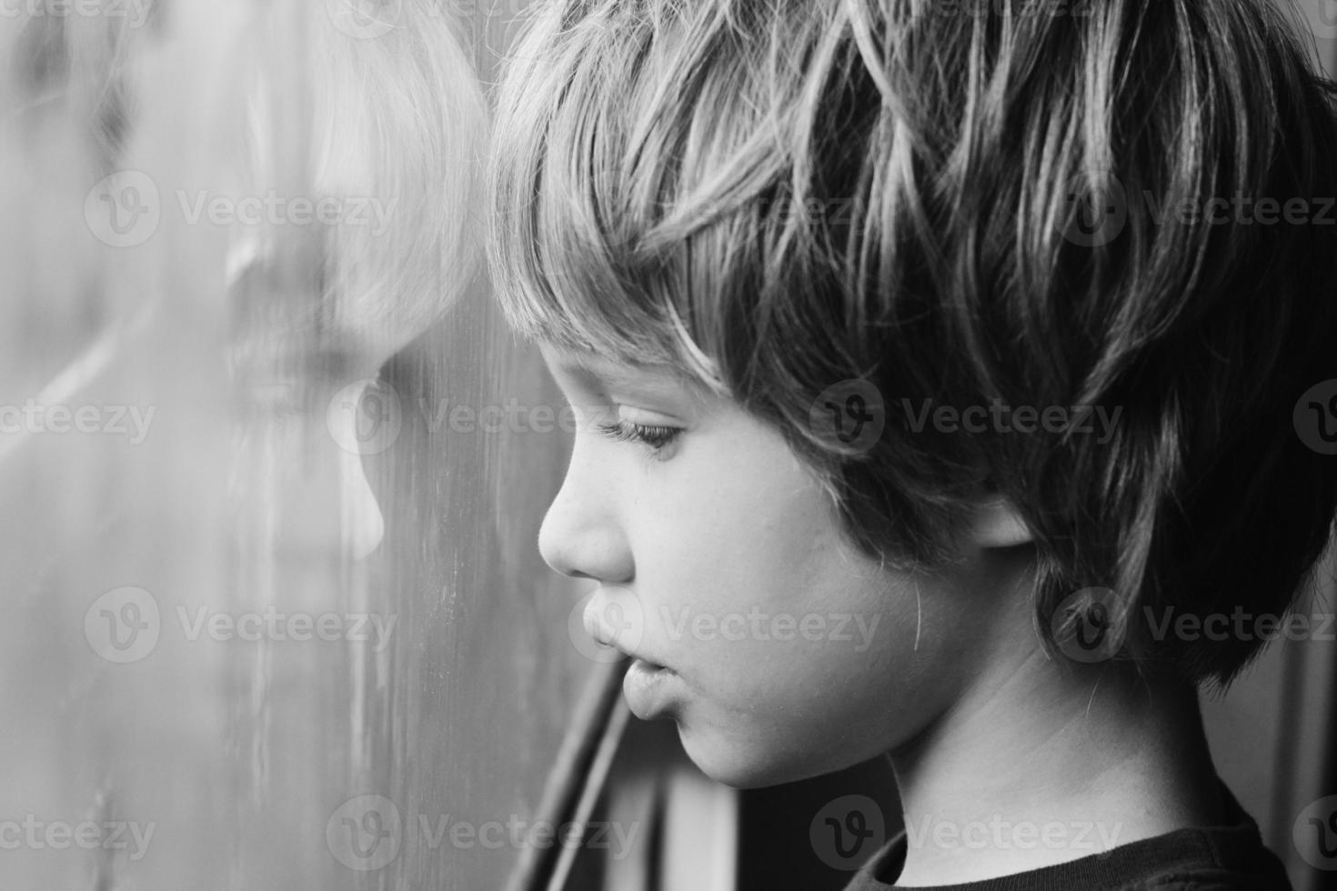 süßer Junge, der durch das Fenster schaut foto