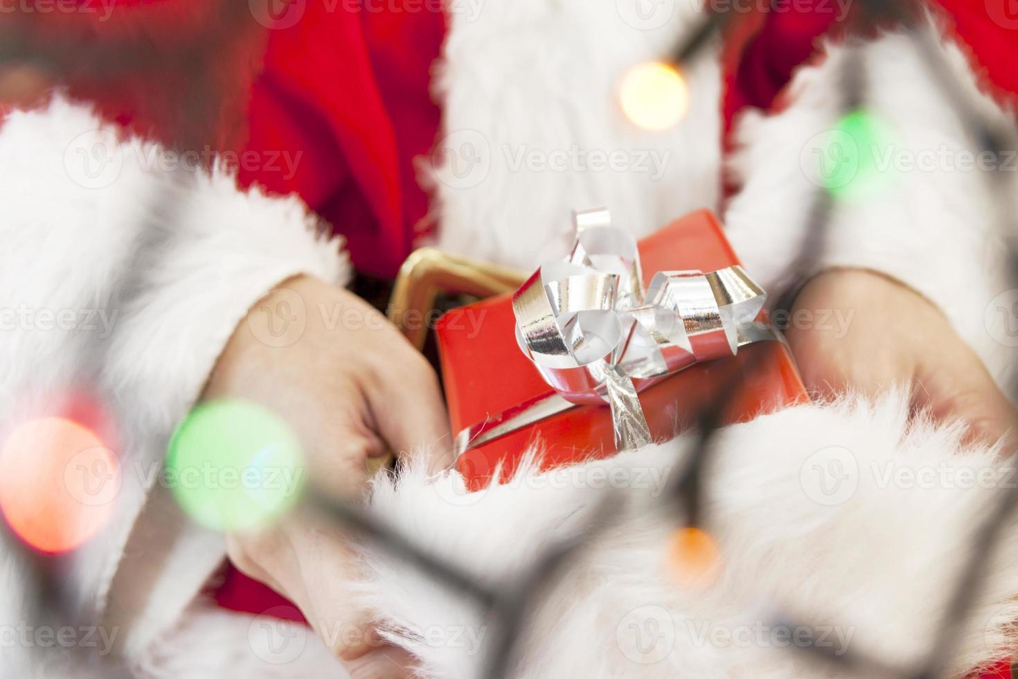 Weihnachtsmann zeigt ein Weihnachtsgeschenk foto