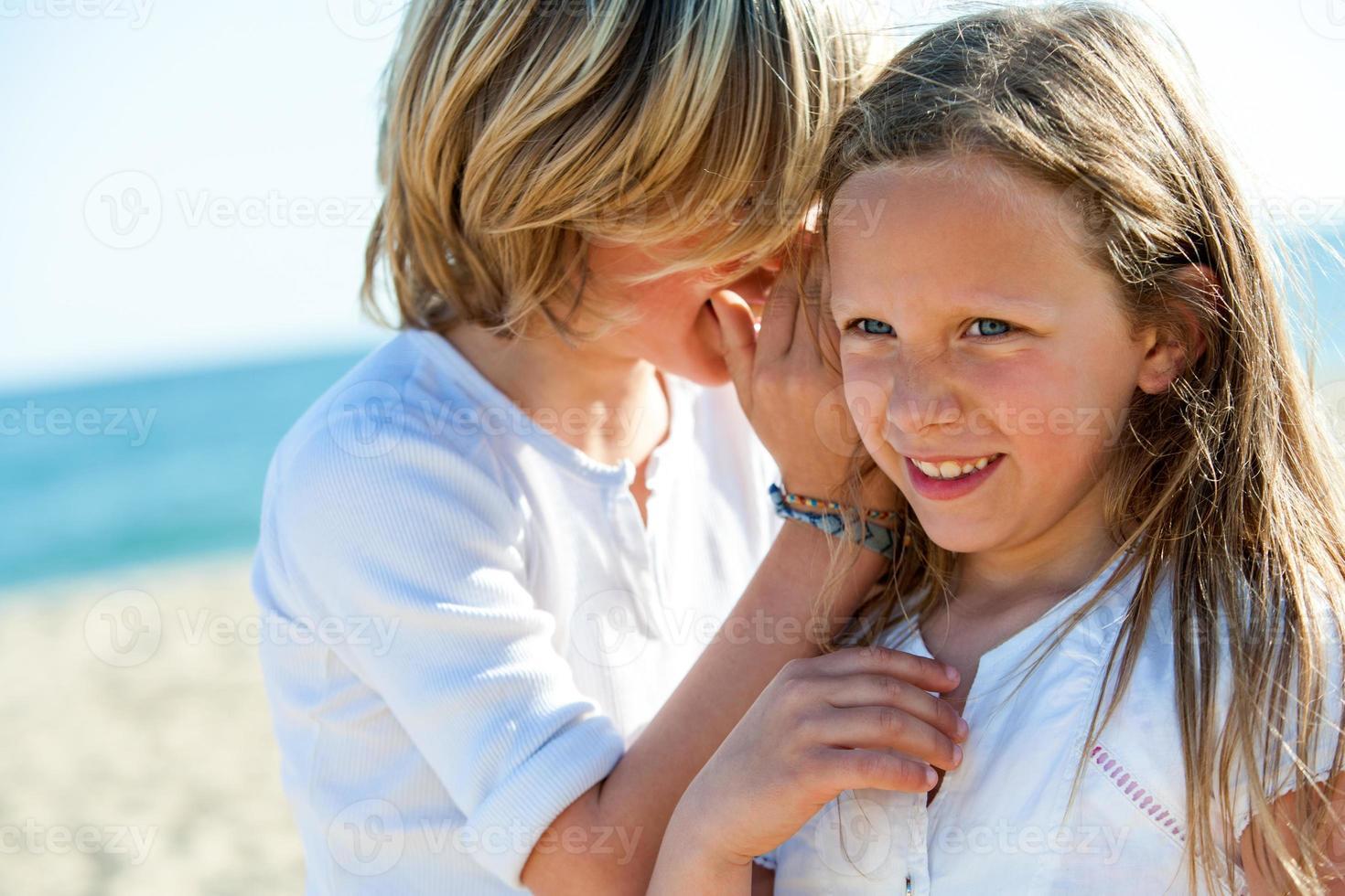 Junge flüstert Mädchen im Freien Geheimnisse zu. foto