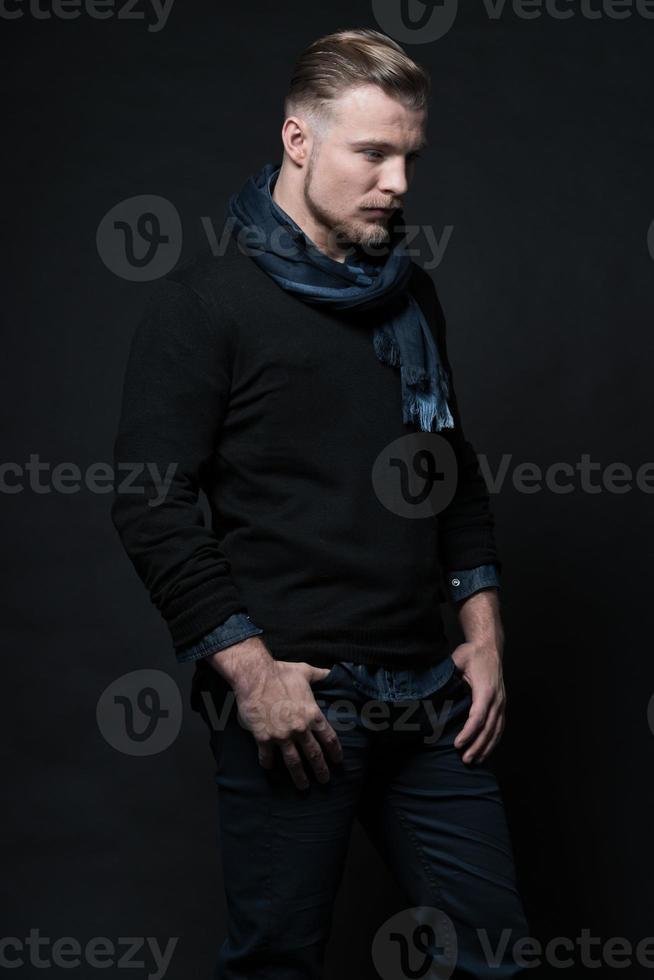 Mann Wintermode. trägt schwarzen Pullover und Schal. blondes Haar. foto