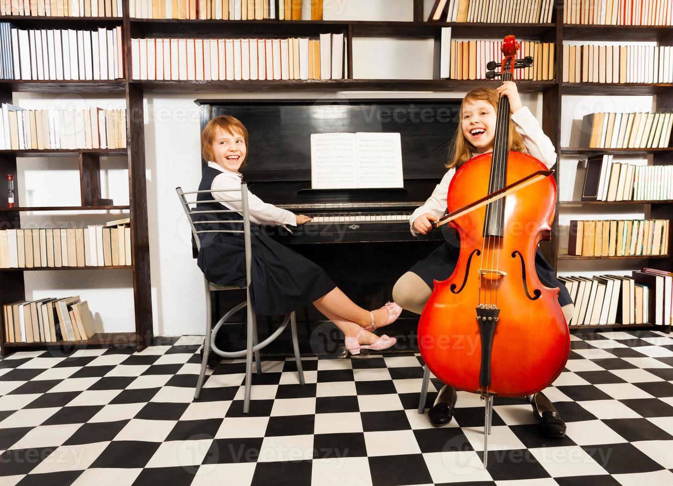 Mädchen spielen auf Violoncello und Klavier foto