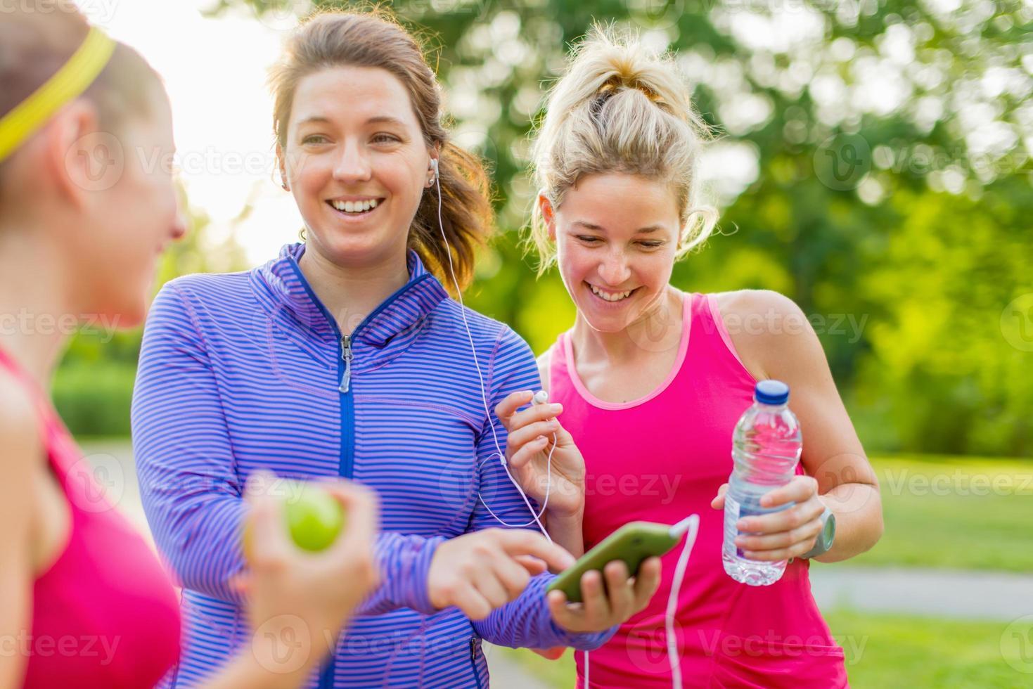 Fitness-Girls haben Spaß daran, Musik mit Ohrhörern im Park zu hören foto