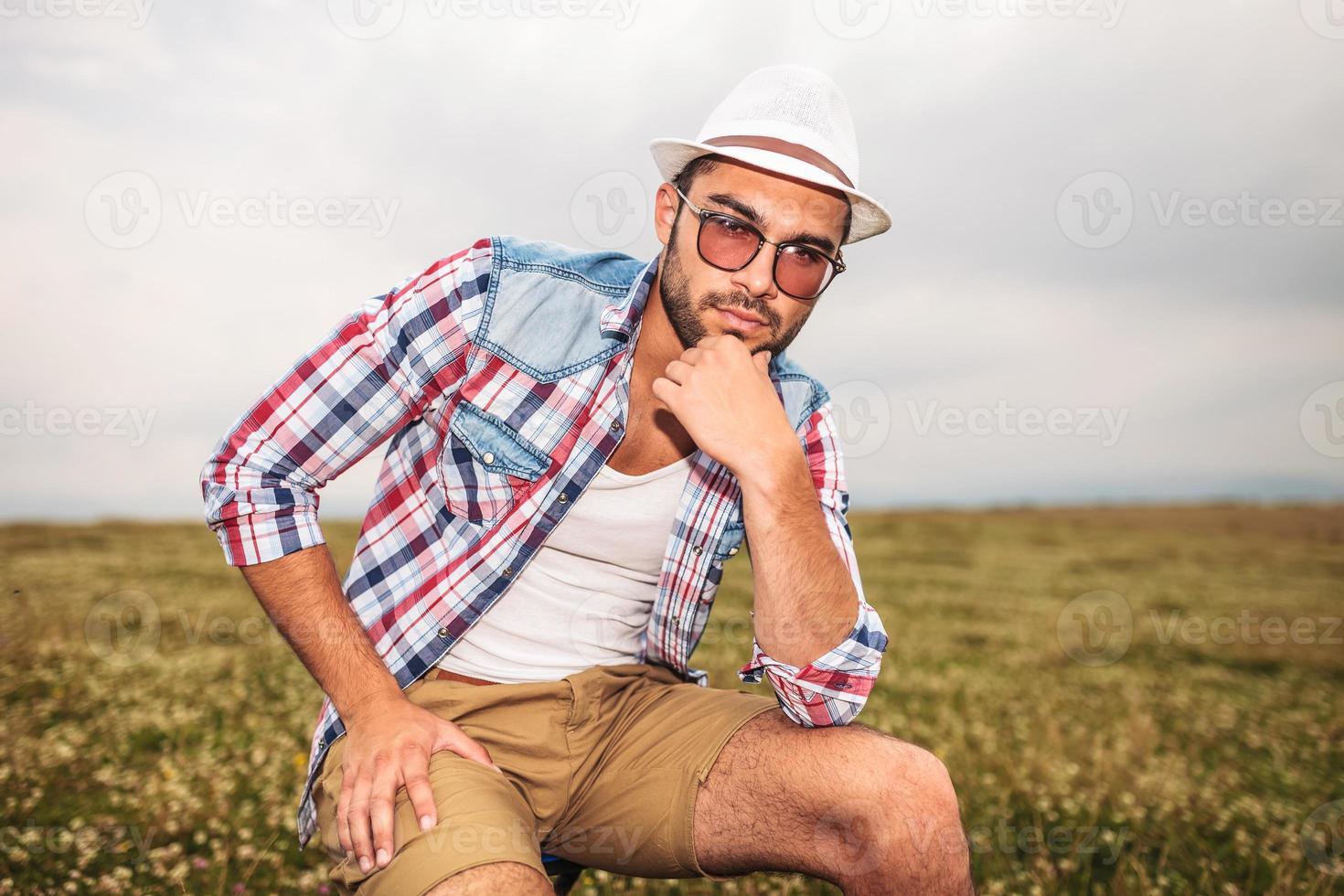 Mann mit Hut denkt, während er auf einem Stuhl sitzt foto
