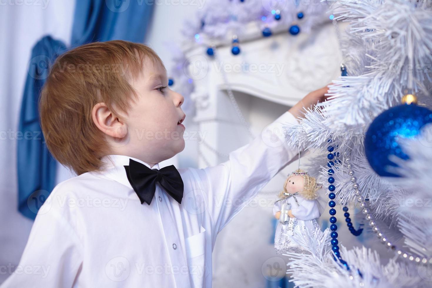 Junge in Hemd und Fliege schmückt einen Weihnachtsbaum foto