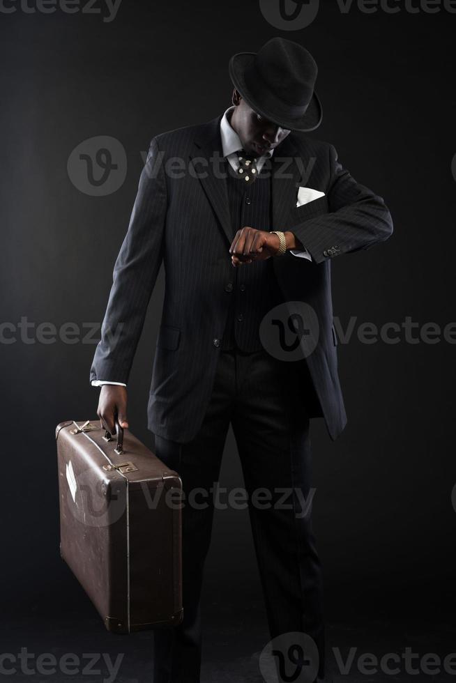 Retro Afroamerikaner Reisender, der gestreiften Anzug und Krawatte trägt. foto