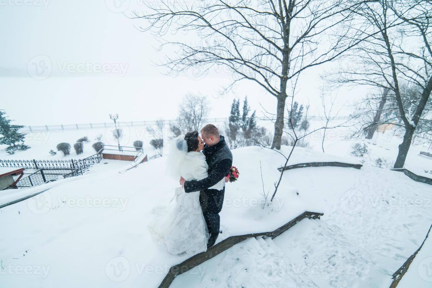 Braut und Bräutigam gehen im Schnee foto