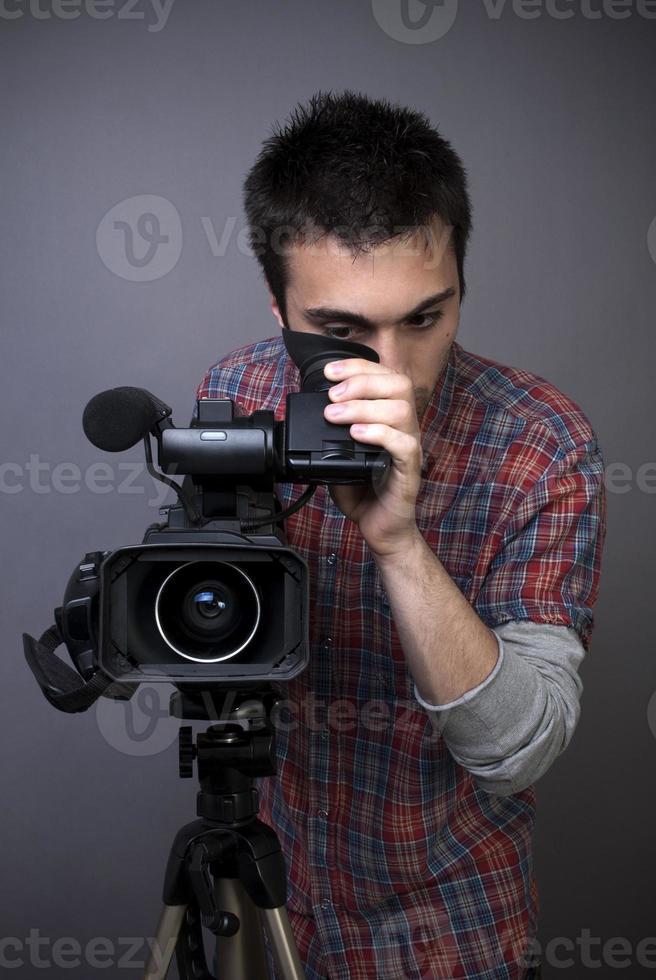 junger Mann mit professionellem Video-Camcorder foto