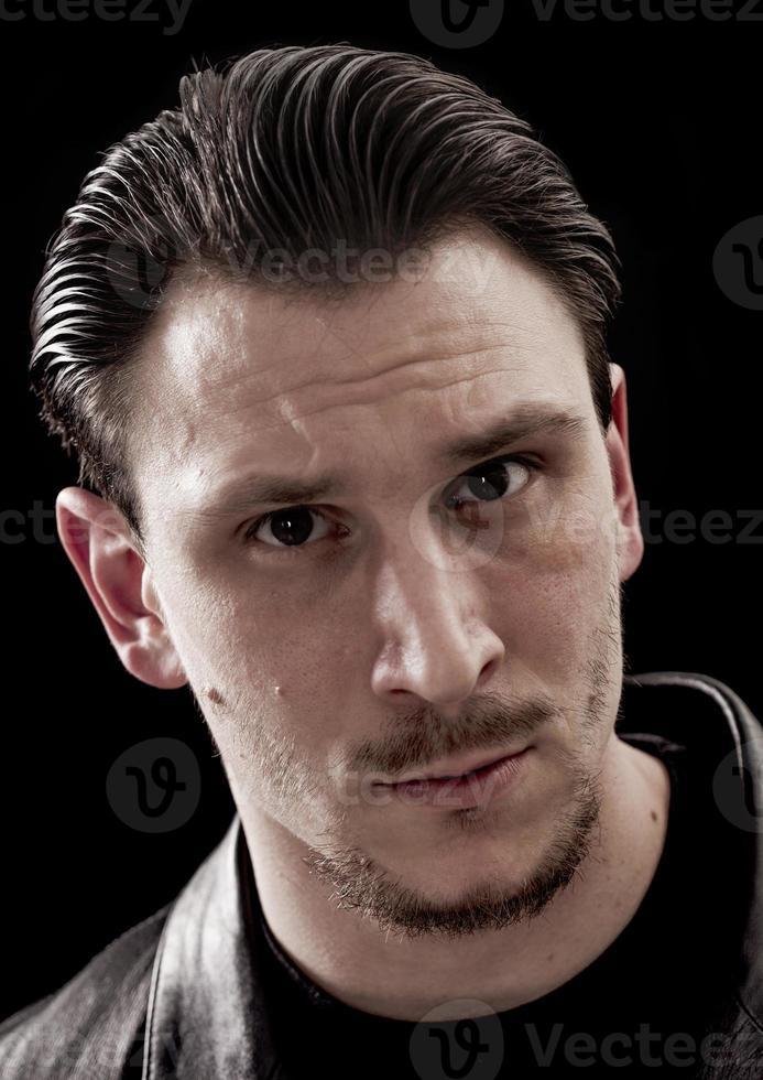 hübsches Mann-Nahaufnahmeporträt auf schwarzem Hintergrund foto