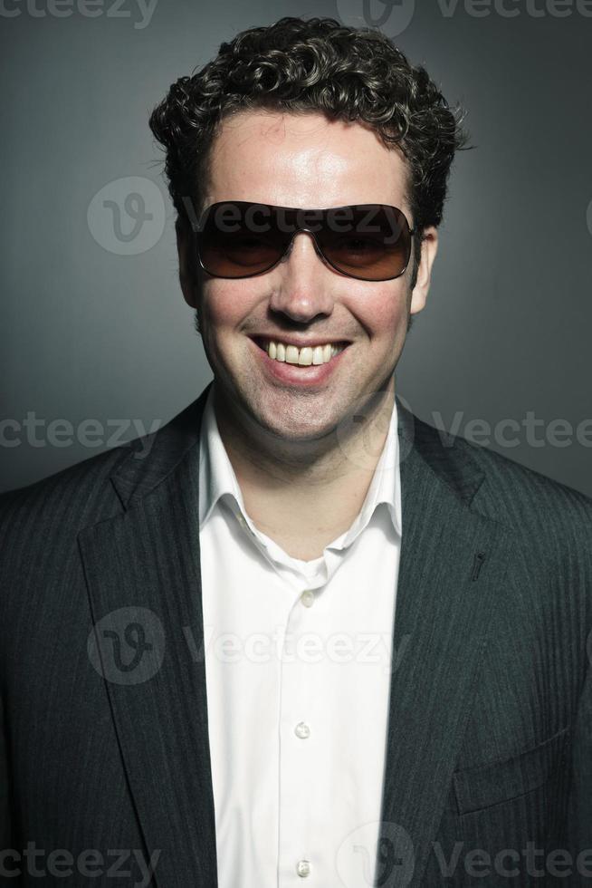 Studioporträt des Geschäftsmannes, der Sonnenbrille gegen grauen Hintergrund trägt. foto