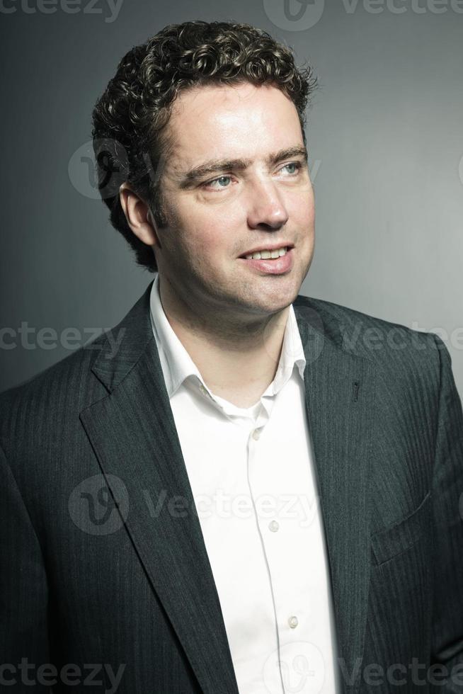 Studioporträt des Geschäftsmannes gegen grauen Hintergrund. foto
