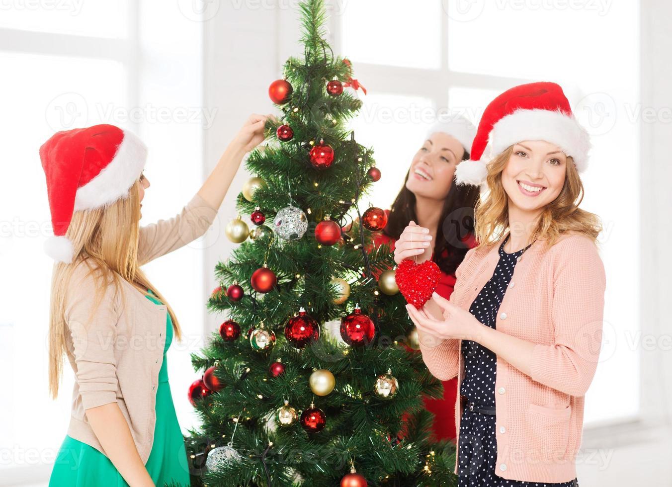 Frauen in Santa Helferhüten schmücken einen Baum foto