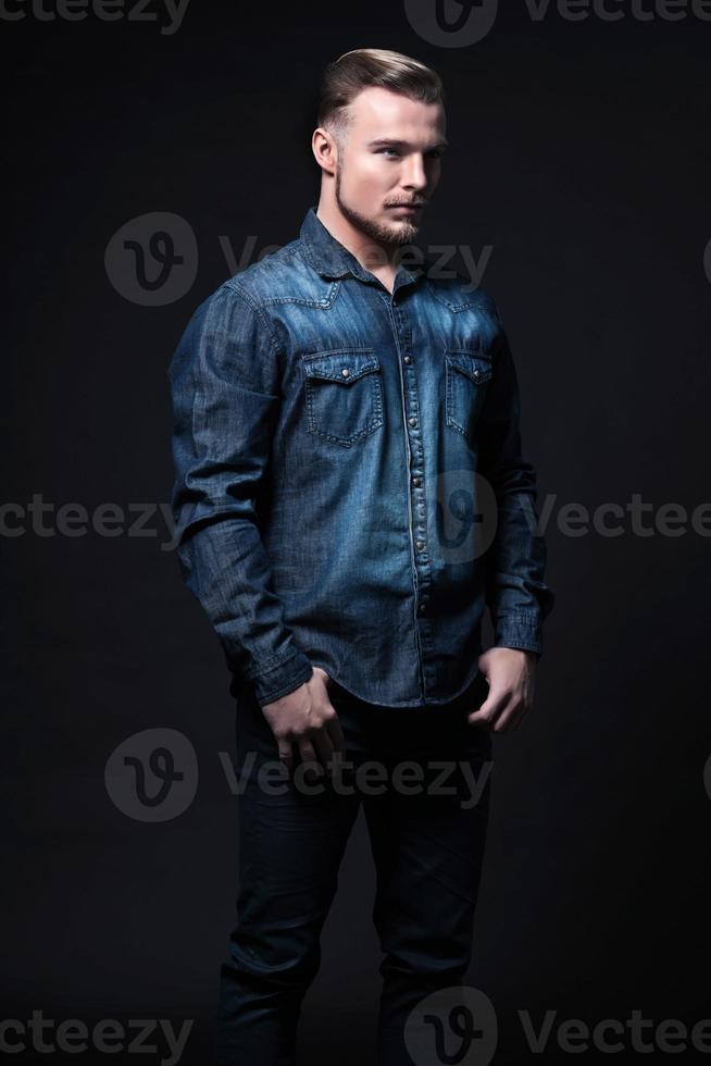 lässiger Wintermode-Mann. trägt ein blaues Jeanshemd und eine Hose. foto
