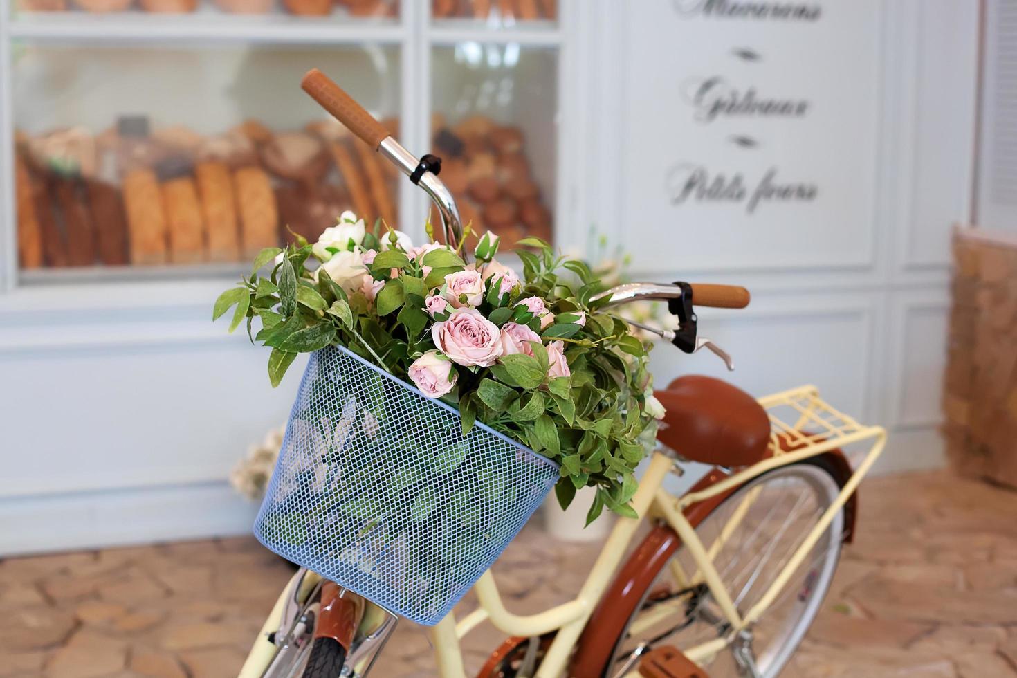 Fahrrad mit einem Vintage Weidenkorb mit Rosen foto