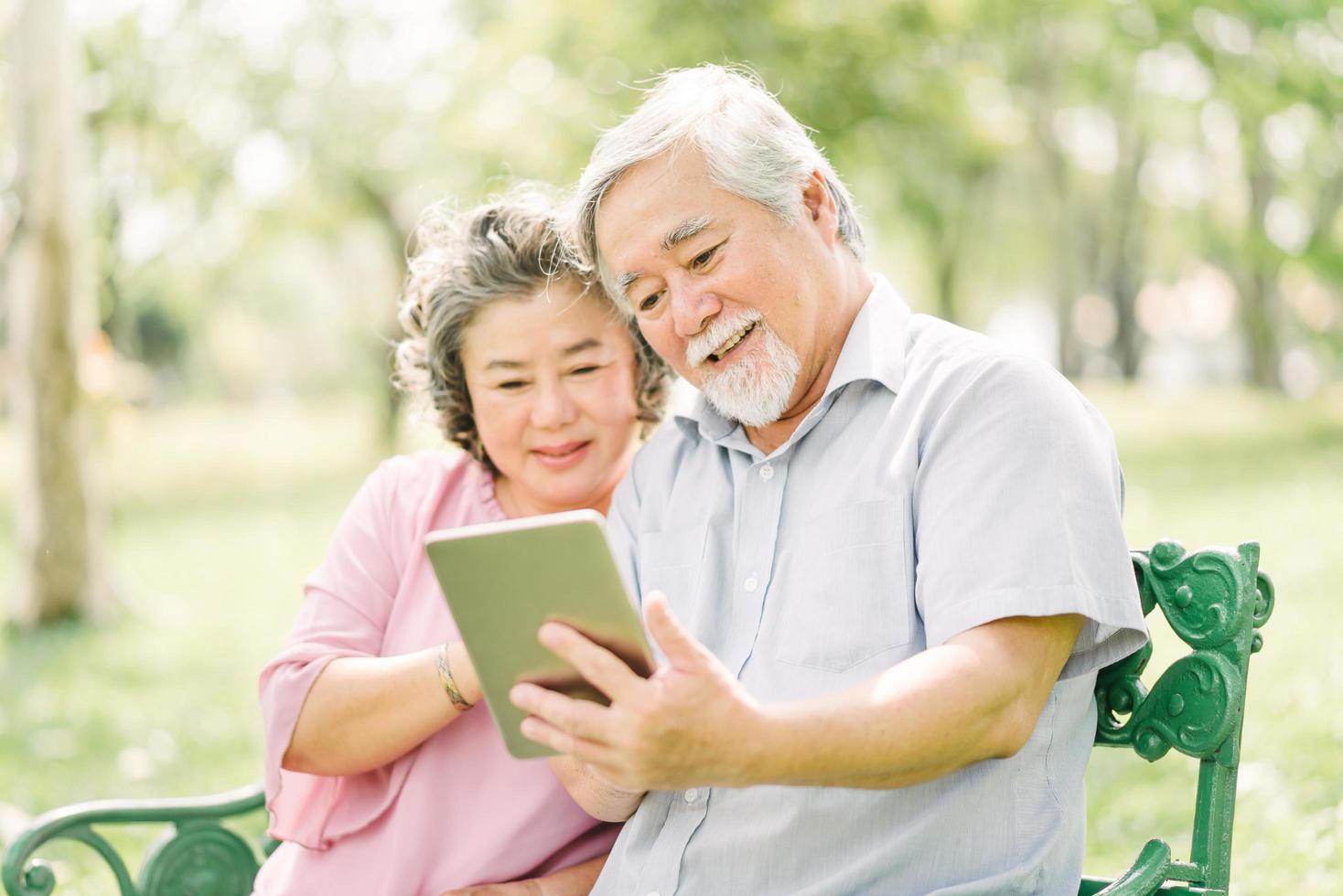 älteres asiatisches Paar mit Tablette im Park foto
