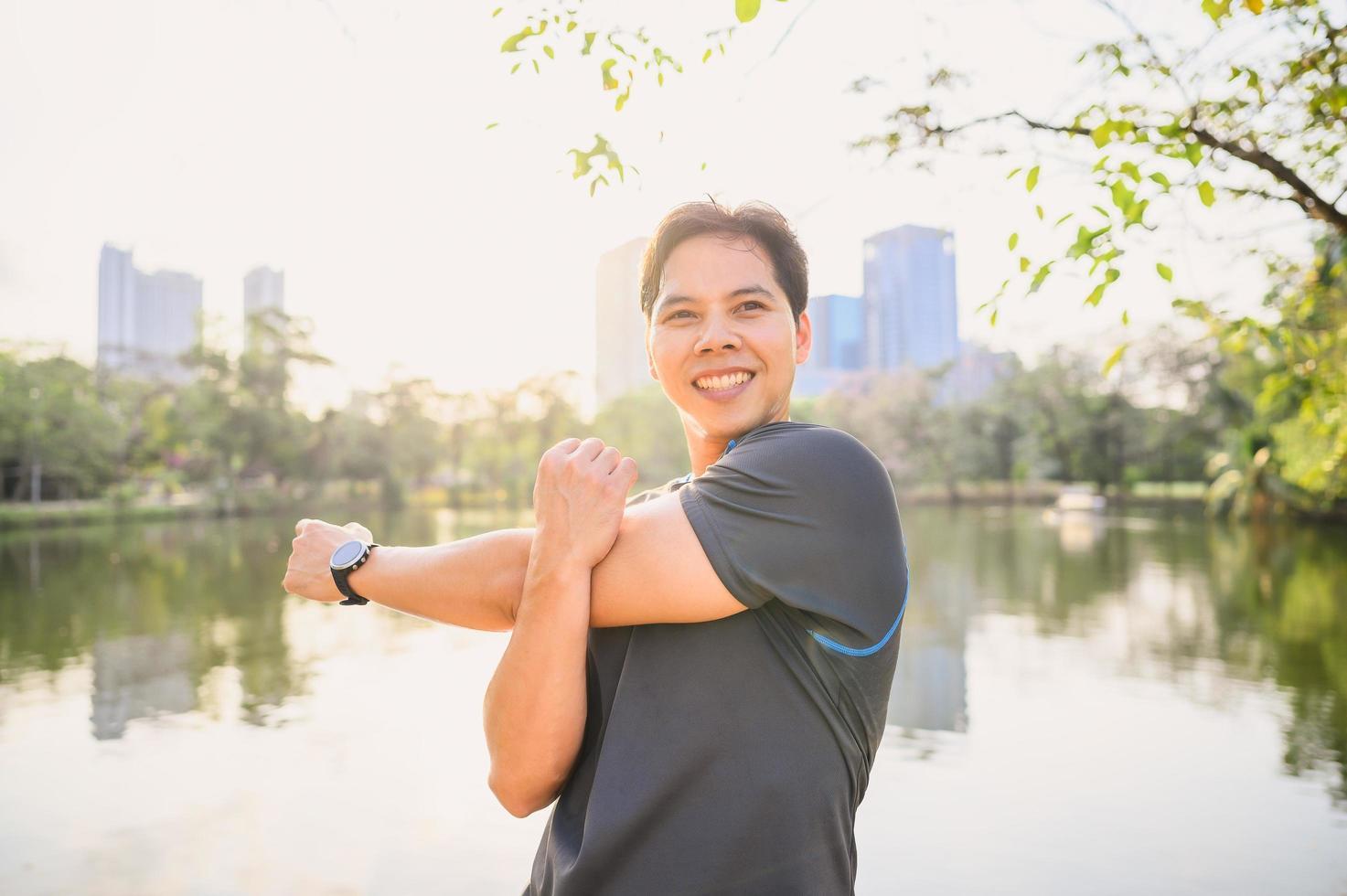 männlicher Läufer, der Schulterdehnungsübung macht foto