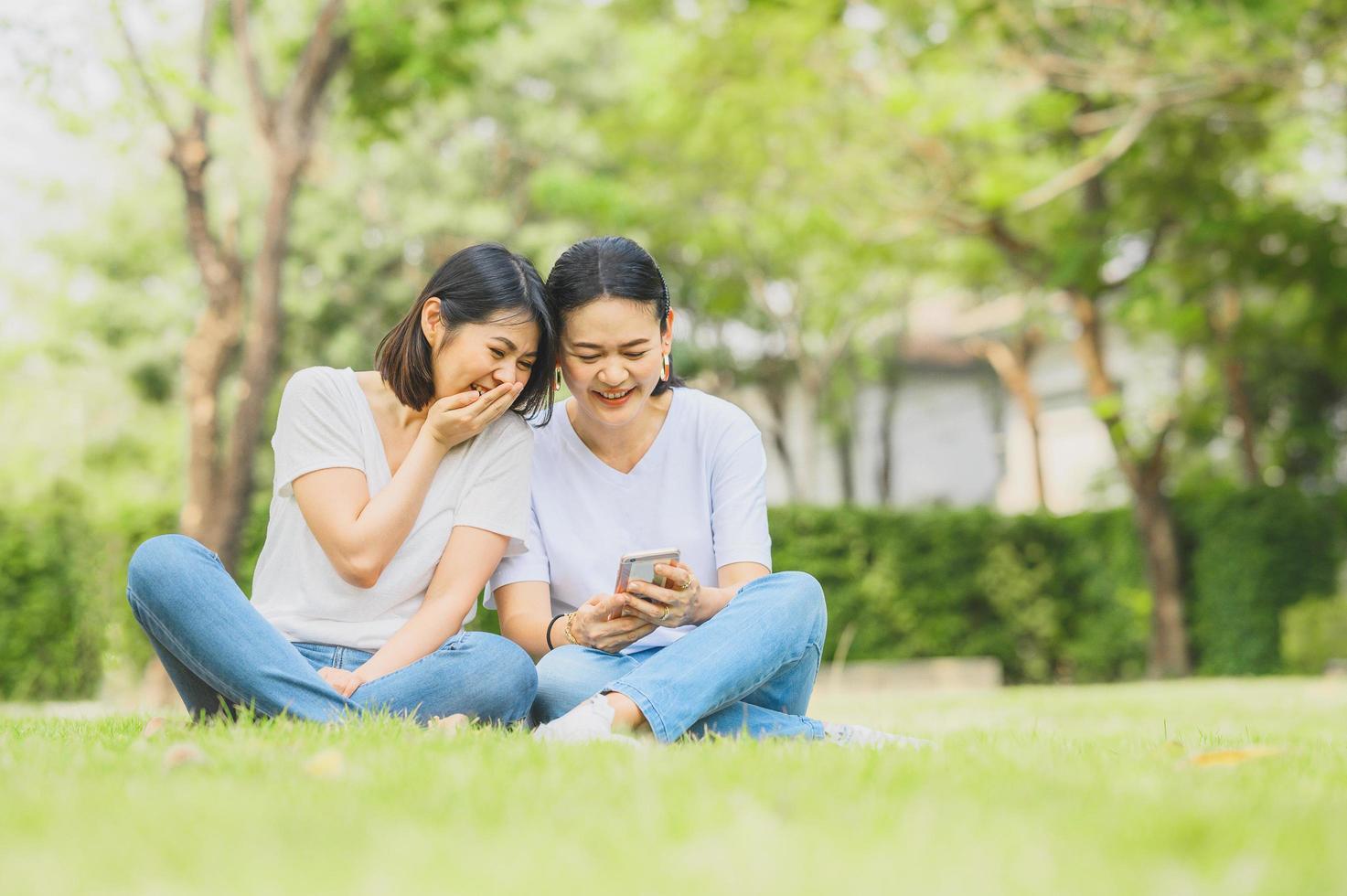 asiatische Frauen lachen, während sie Smartphone im Freien benutzen foto