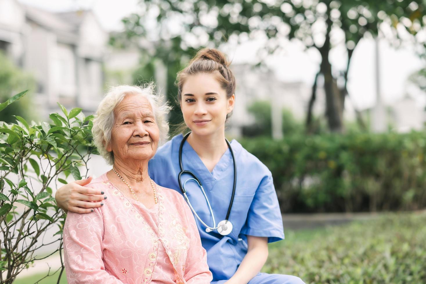 Pflegekraft, die Senior im Park umarmt foto