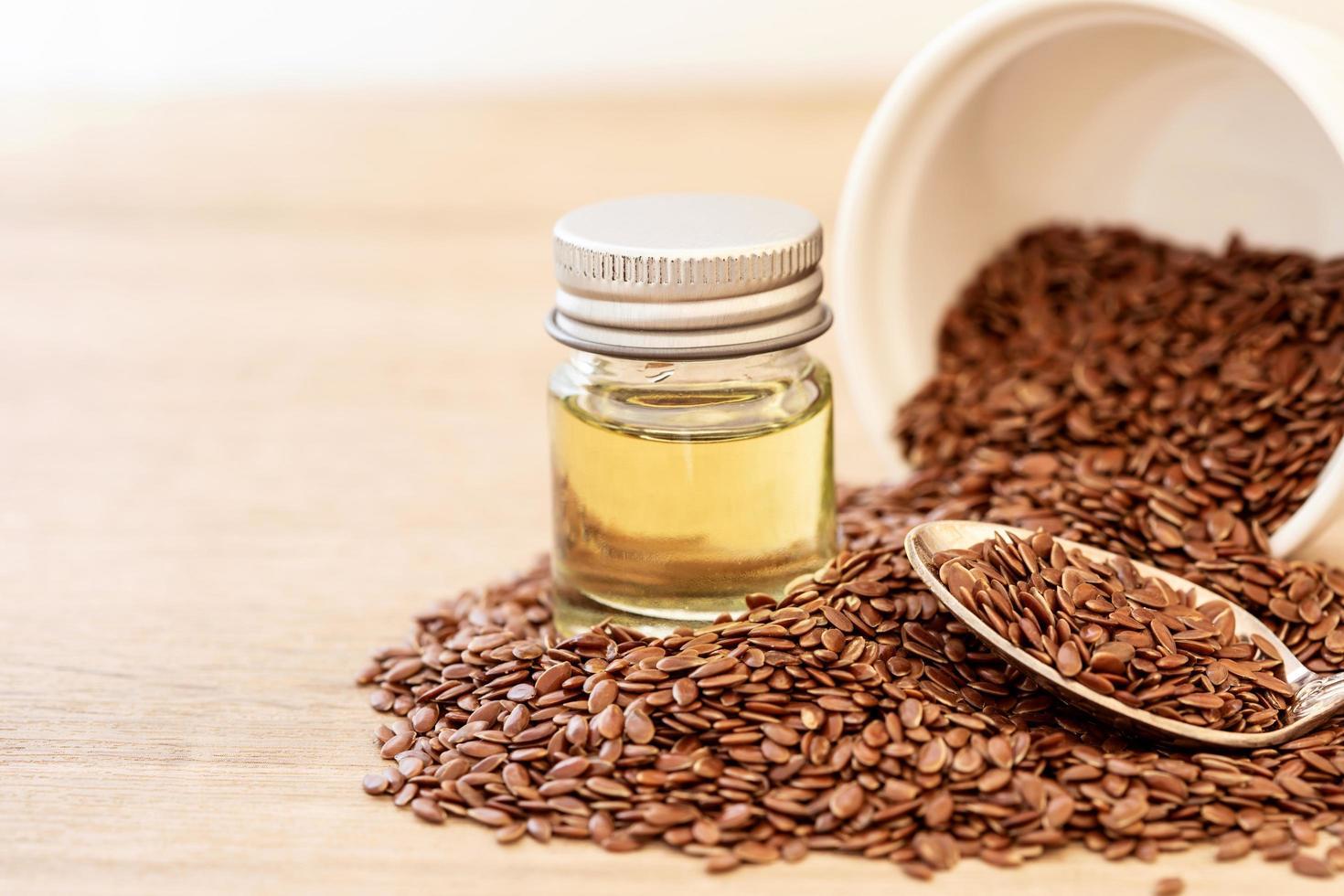 Nahaufnahme von Leinsamen und Leinsamenöl auf Holztisch foto
