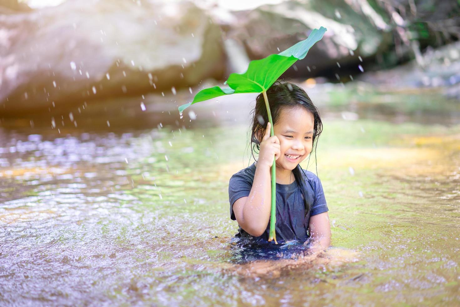 kleines asiatisches Mädchen, das im Wasser spielt foto