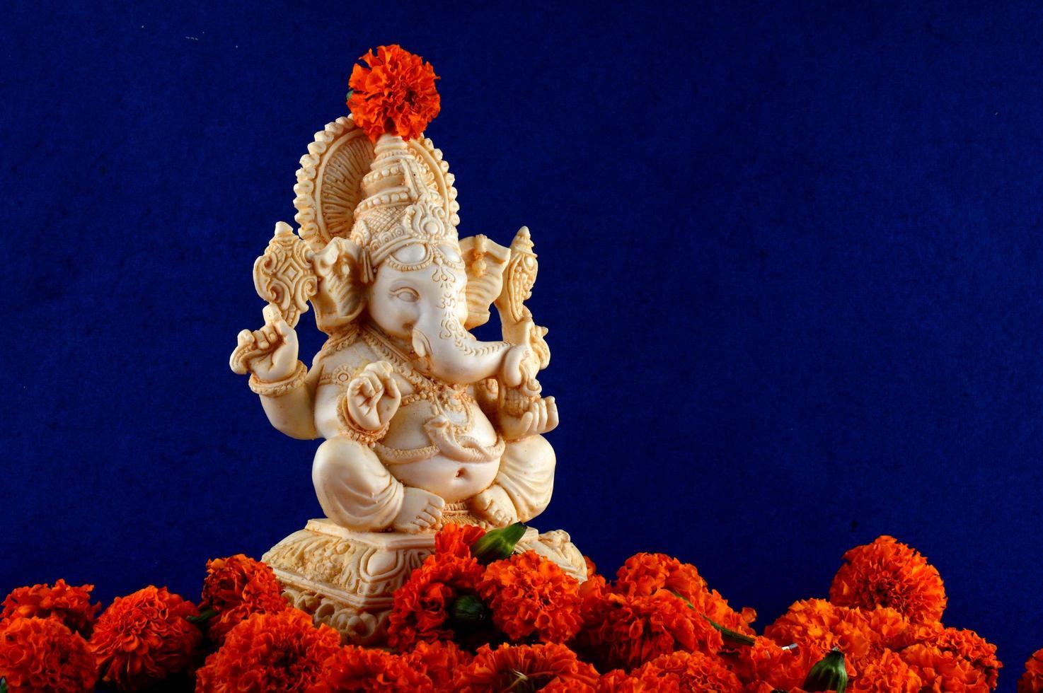 Ganesha-Statue mit roten Blumen foto
