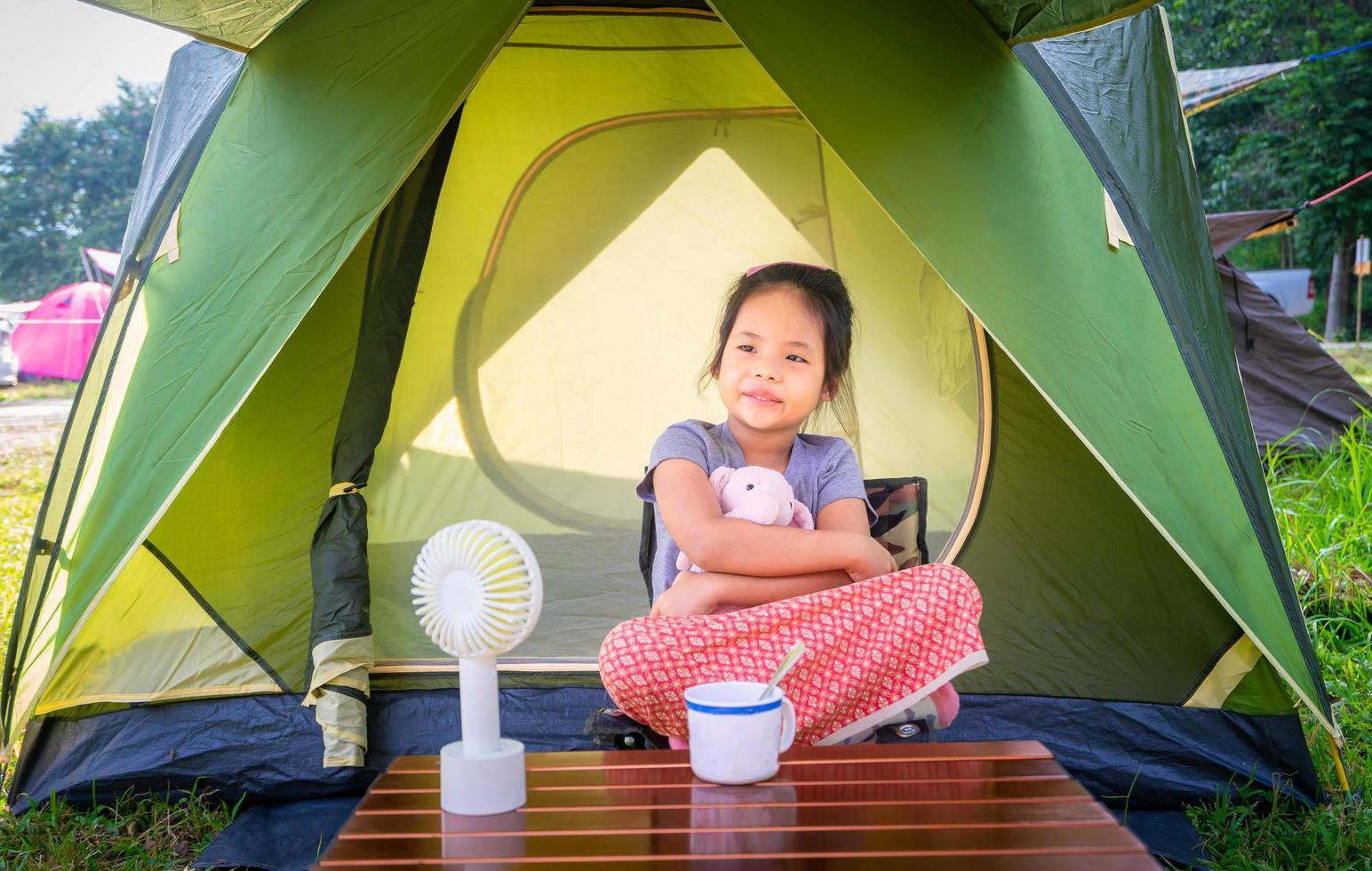 junges Mädchen, das im Zelt beim Zelten sitzt foto
