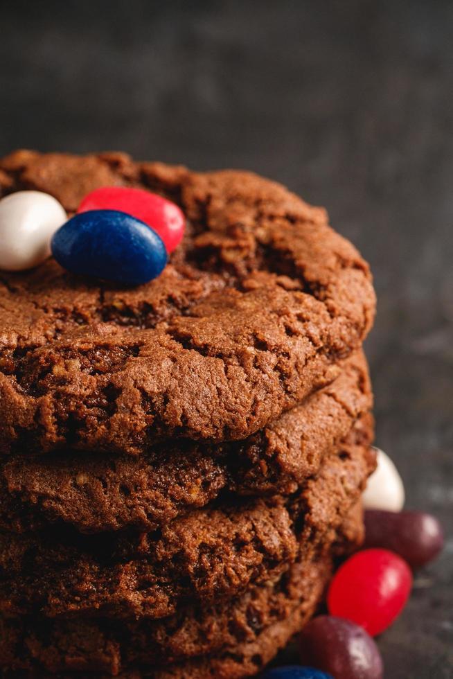 Schokoladenplätzchen gestapelt auf strukturiertem dunklem schwarzem Hintergrund foto