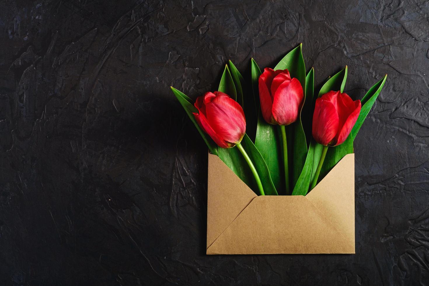 rote Blumen in einem Papierumschlag auf strukturiertem dunkelschwarzem Hintergrund foto
