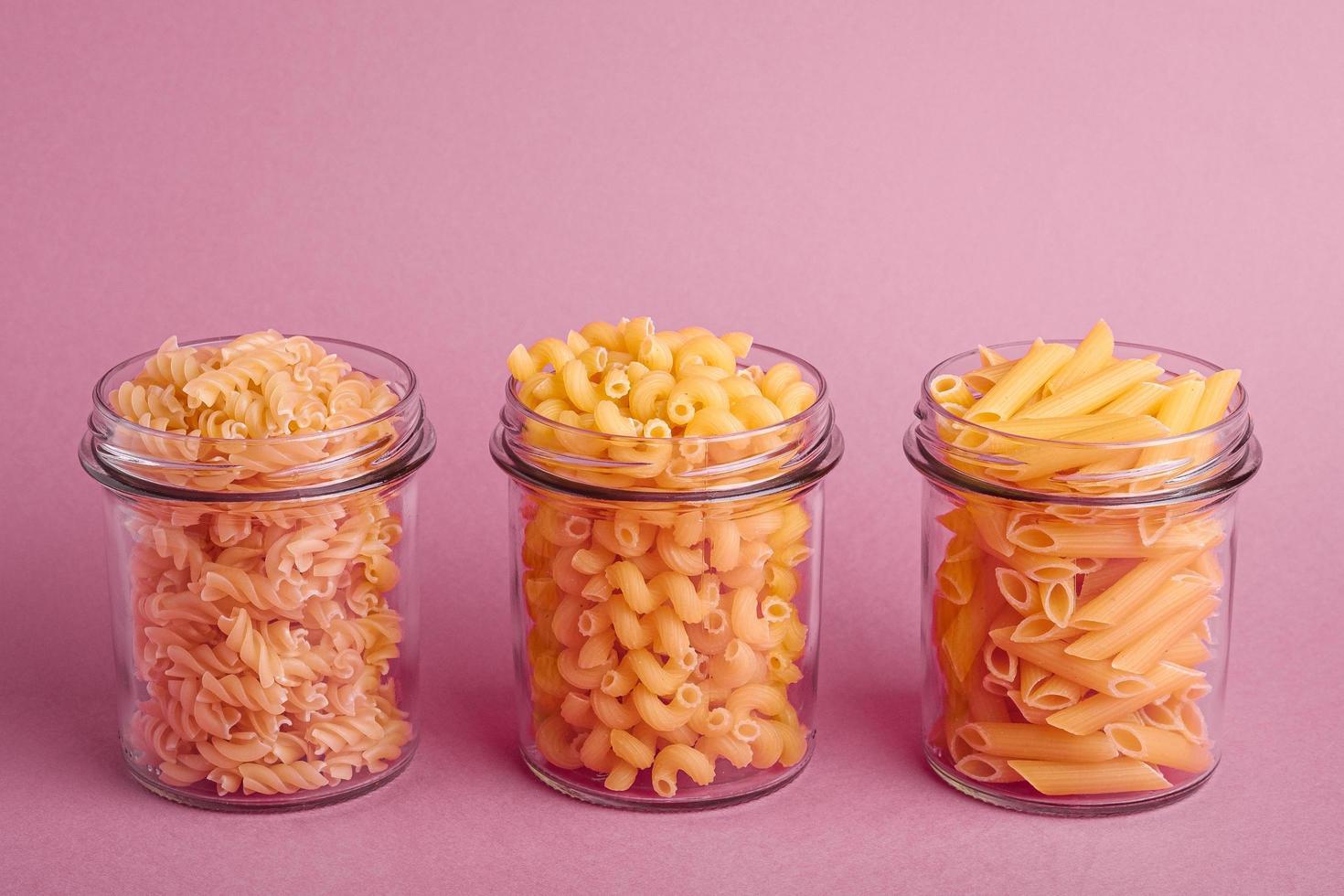 Vielzahl von ungekochten goldenen Weizennudeln auf minimalem rosa Hintergrund foto