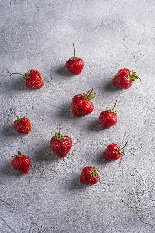Erdbeeren in einer Gruppe auf grauem Hintergrund foto