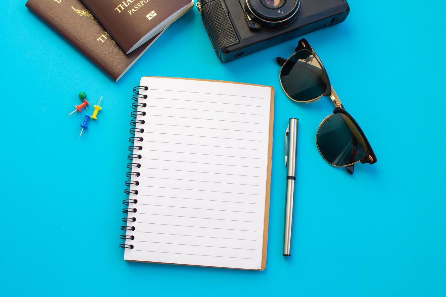 flache Notizbuchlage, umgeben von Reiseartikeln foto