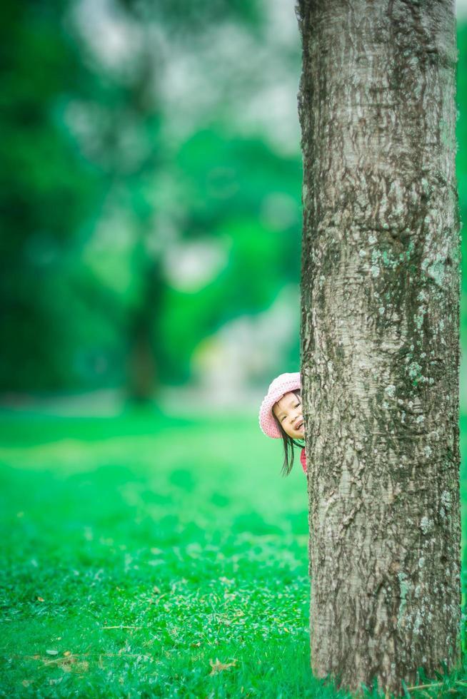 kleines asiatisches Mädchen, das sich hinter den Baum im Wald schleicht foto
